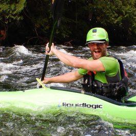 man smiling in green kayak on river