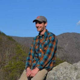 man in plaid shirt sitting on a rock in the outdoors