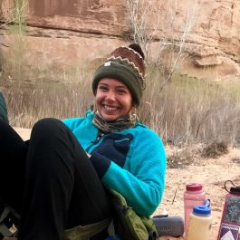 Girl in blue jacket and beanie in desert