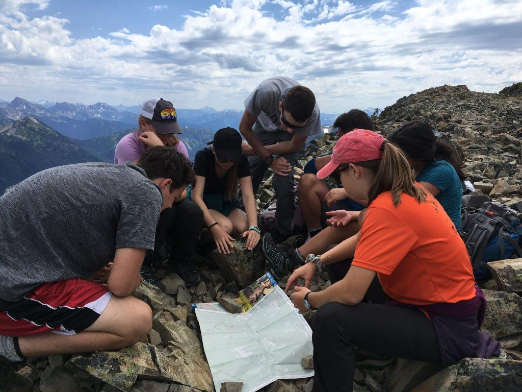 teenagers navigating map british columbia mountains