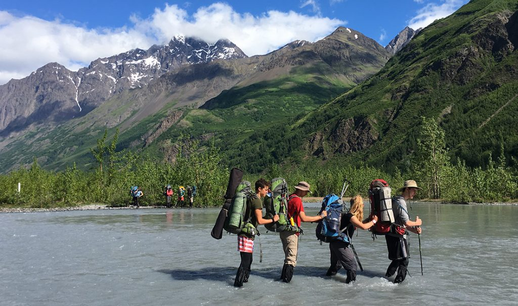teenagers crossing a river in alaska with backpacks