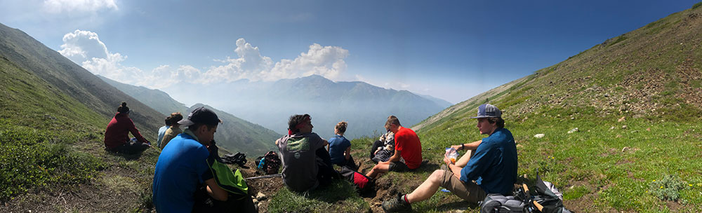 teenagers sitting for lunch while hiking in mountains in alaska