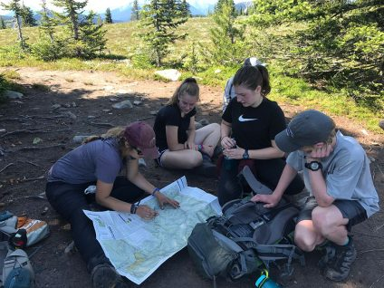 teenagers looking at a map while hiking in british columbia