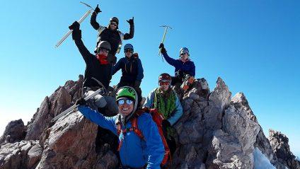 teenagers standing on mount shasta mountain summit
