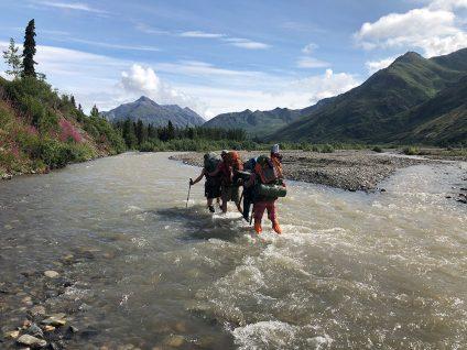 teenagers crossing a river in alaska