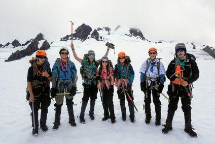 teenagers climbing and summiting mt. olympus in washington