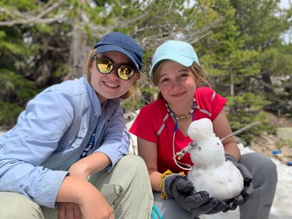 teenage girls hiking in colorado with snowballs