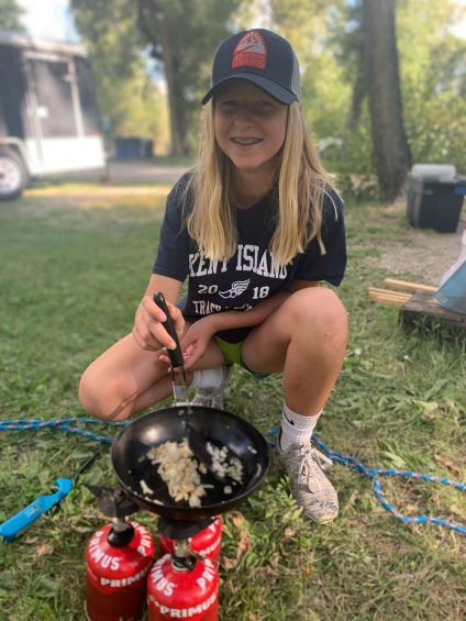 teenage girl cooking on camp stove in the outdoors