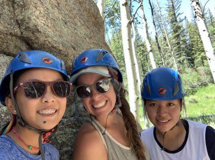 teenage girls rock climbing in colorado wearing helmets