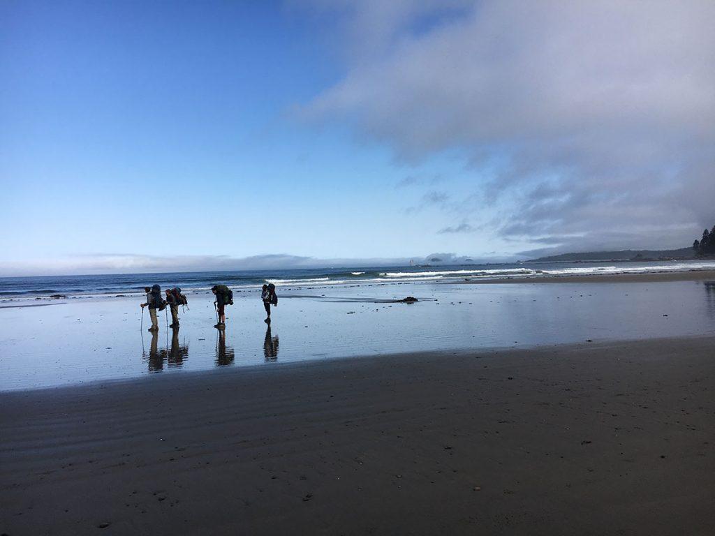 teenagers hiking on beach on olympic peninsula washington