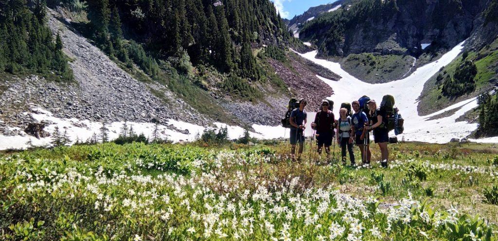 teenagers hiking in goat rocks wilderness washington in wildflower fields