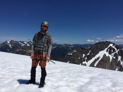 man in beard standing on snowy mountain