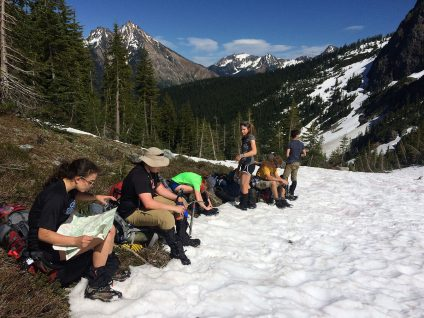 teenage boys and girls reading a map while hiking