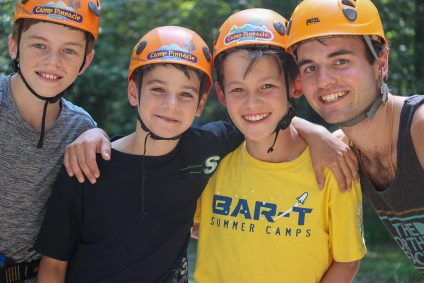 male campers and male counselors at summer camp wearing helmets