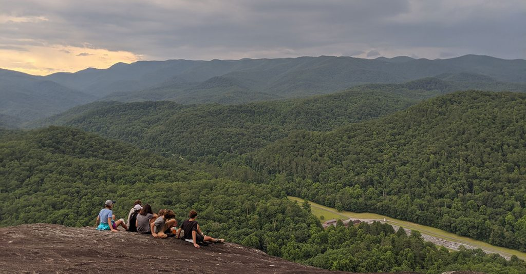 teenage boys and girls sitting on a rock face in front of a mountain view