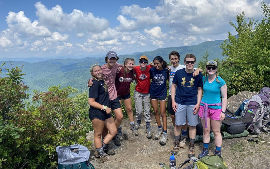 teenage boys and girls hiking with backpacks in the mountains
